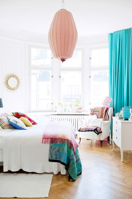 turquoise curtains and bedspreads and pillows add cheer to this white bedroom