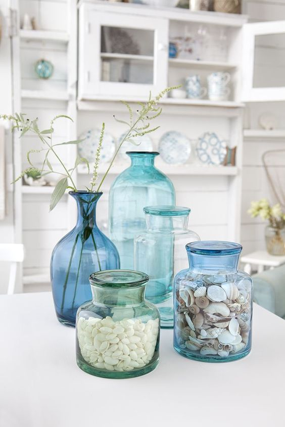 aqua, blue and turquoise glass bottles with shells and herbs for a Mediterranean arrangement