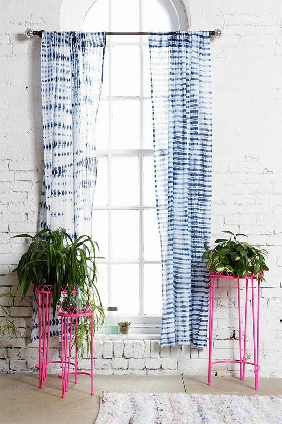 shibori curtains stand out in front of whitewashed brick walls