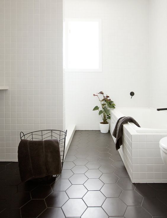 small white square tiles and matte black hex ones create a chic Scandinavian-inspired space