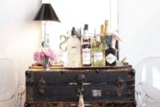28 a large black vintage chest is used as a home bar, and everything necessary is inside it