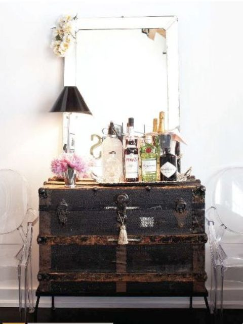 a large black vintage chest is used as a home bar, and everything necessary is inside it