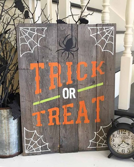 a simple pallet Trick Or Treat sign with webs, spiders and in bold colors
