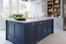 28 a white kitchen with a dark blue kitchen island and a white countertop