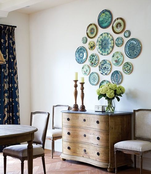 blue and green decorative plates styled on the wall of a dining room