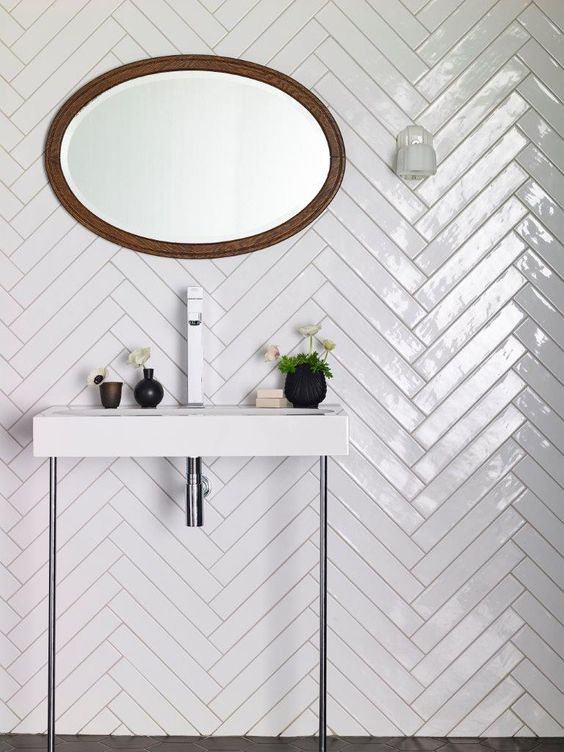 glossy white tiles clad in a herringbone pattern to make the bathroom more eye-catching