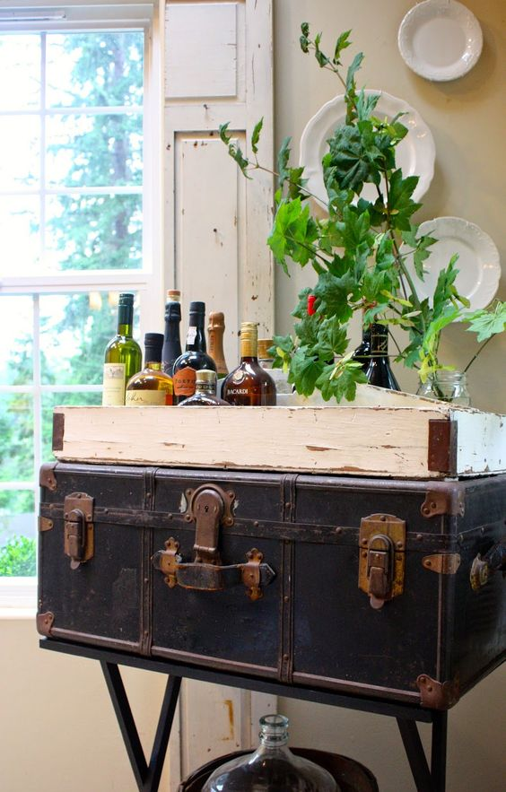 a vintage trunk placed on metal legs is used as a home bar