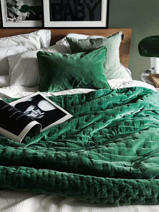 an emerald bedspread and pillow helps to follow the velvet trend and makes the bed inviting