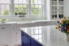 30 a white kitchen with an electric blue island that hints on its seaside theme