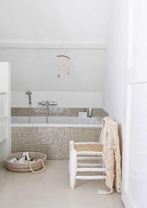 tiny glossy beige tiles civer the bathtub and the zone around it attracting attention