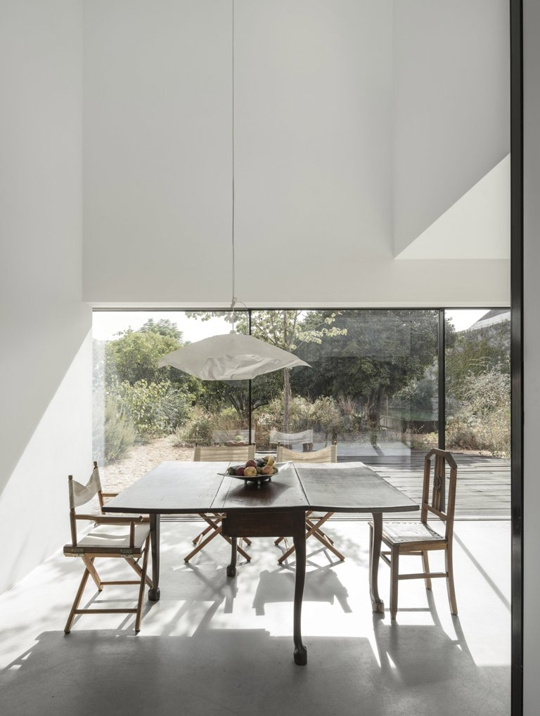 Inside the house is modern, done with white and some rustic furniture - white color reflects light very well