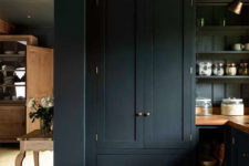02 The cabinetry is black with brass handles, and warm wooden kitchne countertops contrast with this color