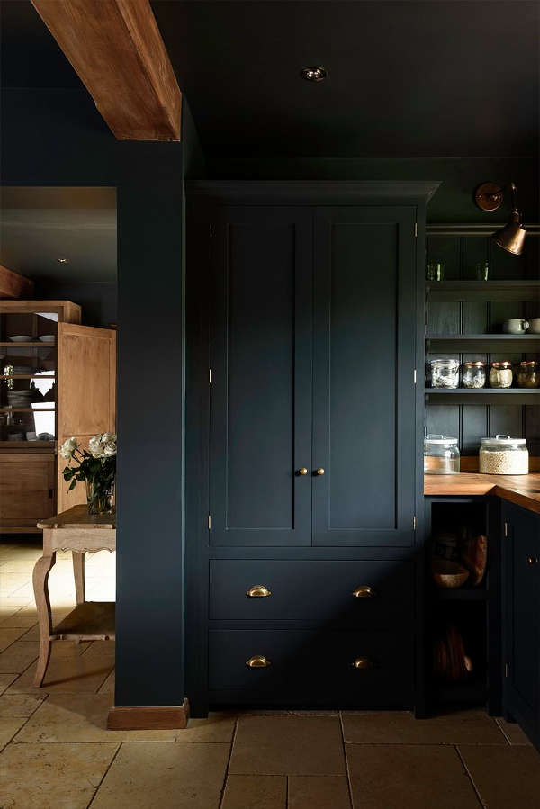 The cabinetry is black with brass handles, and warm wooden kitchne countertops contrast with this color