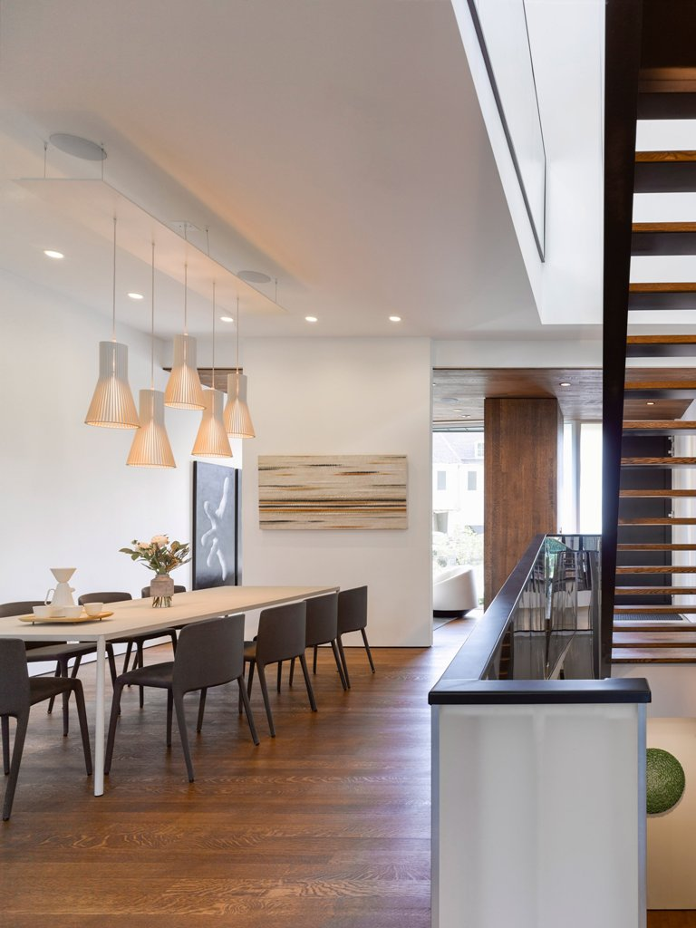 The dining area is done with cool lamps, black modern chairs and a light-colored dining table
