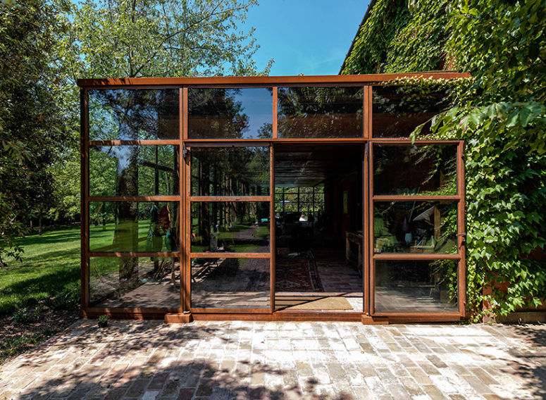 The glass volume is made of glass and corten, and such glazings make one feel outside while being inside