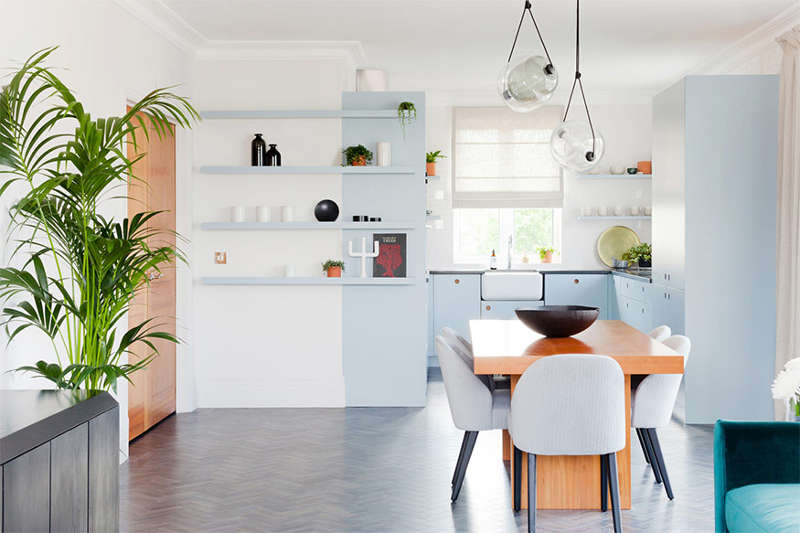 The kitchen is decorated in serenity blue, and it's united with the living space and a dining one