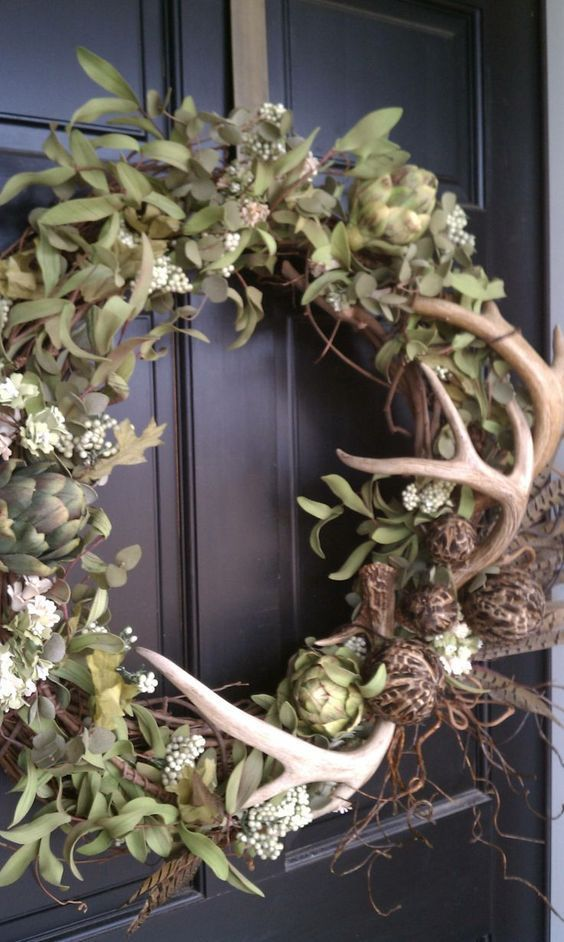 a cool fall wreath with greenery, artichokes, antlers and feathers is great and feels like woodlands
