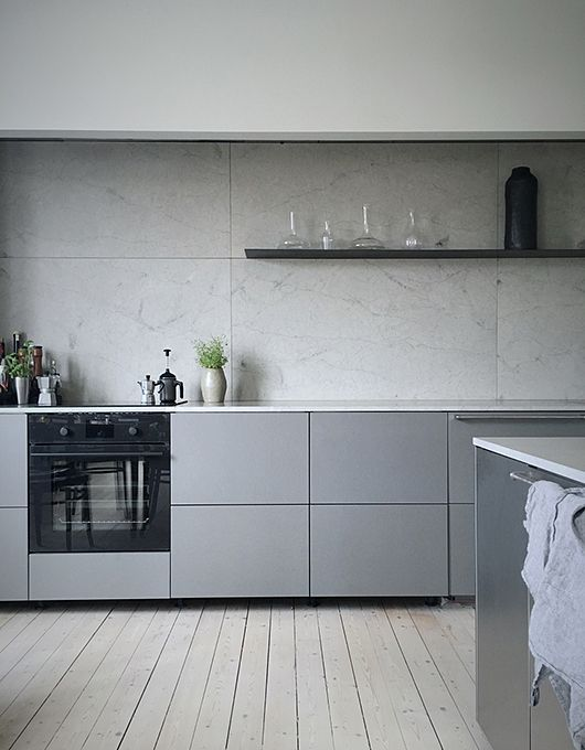 a minimalist grey kitchen with a grey marble backsplash and white countertops for a fresh touch