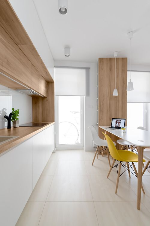 a modern white kitchen with wooden counters and some cabinets for more coziness