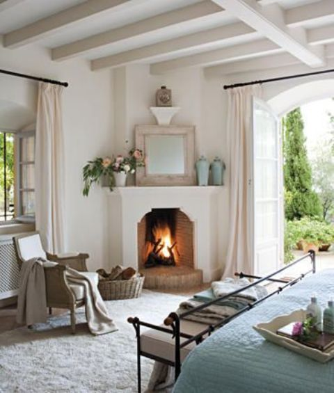 a real fireplace in the corner of your bedroom is sure to add coziness and create a welcoming atmosphere