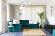 03 The calm and peaceful kitchen is made more eye-catchy with a living space and a bold emerald velvet sofa and a black sideboard