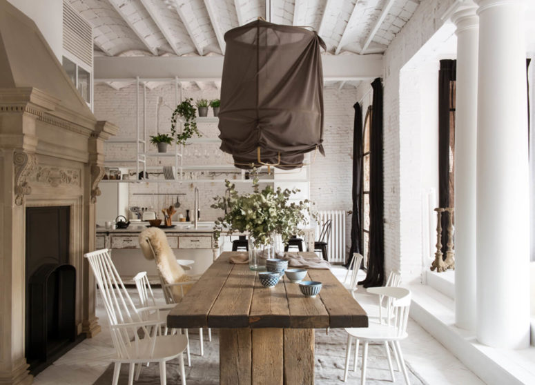 The dining space features a wooden table and some simple white chairs, an antique hearth and fabric-covered lamps