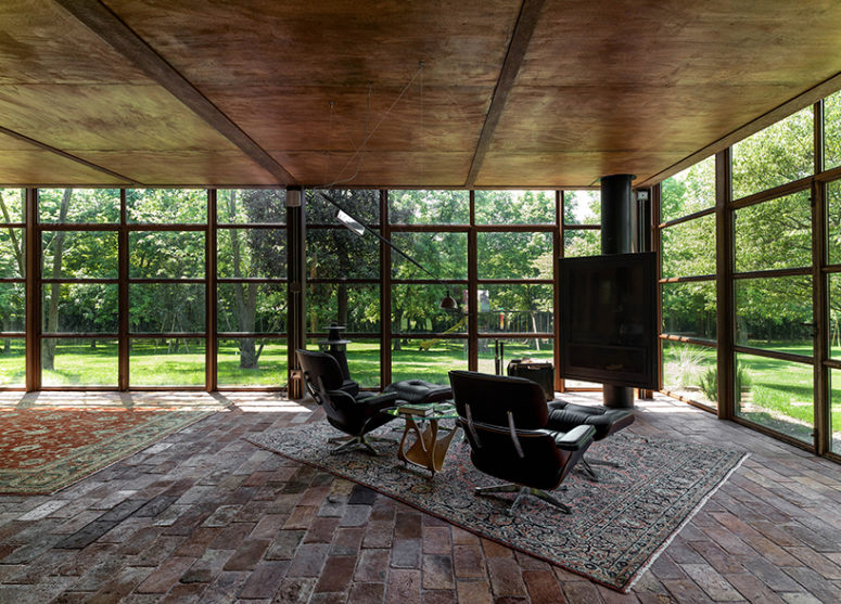 The glass volume totally feels like outside, here's a fireplace sitting space with loungers and a rug for comfort