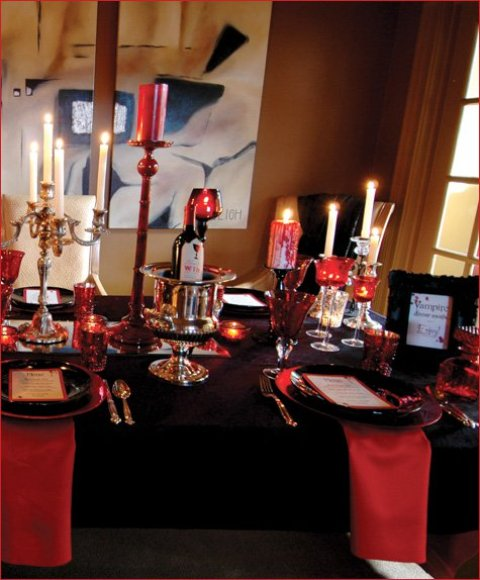 a black and deep red party table with red candles and candle holders, red napkins with a black tablecloth