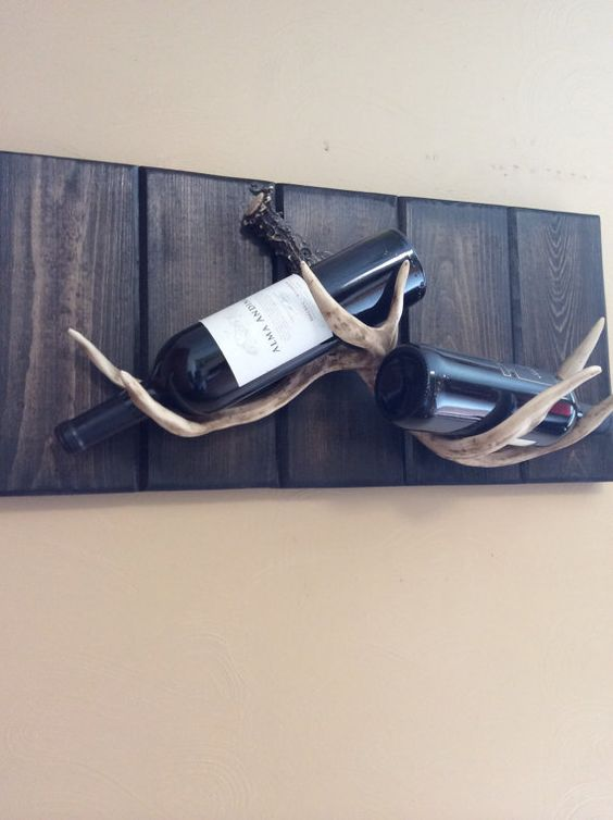 a creative wine rack made of stained wood and antlers is a nice and easy DIY