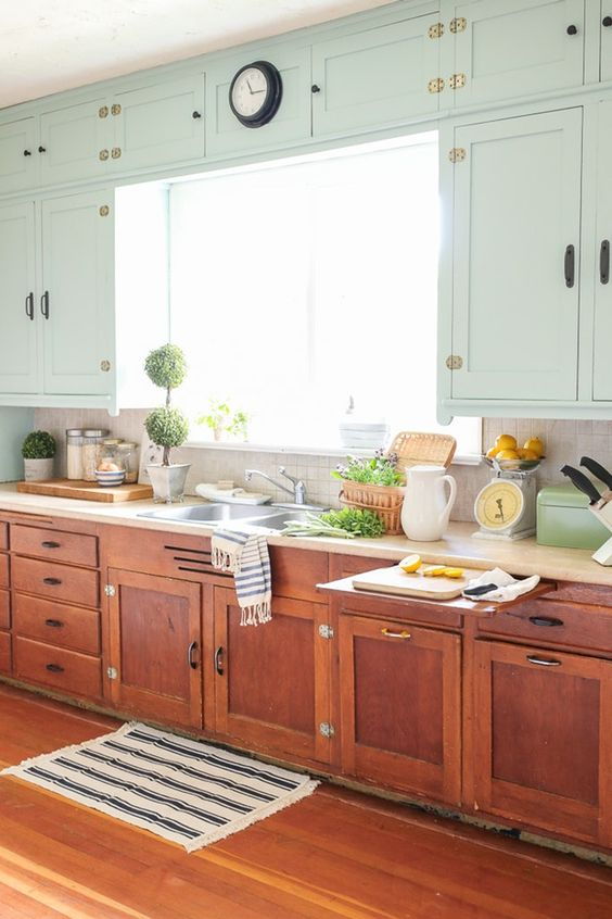 A Farmhouse Kitchen With Neutral Wall Cabinets And Burnt Orange Ones On The Floor