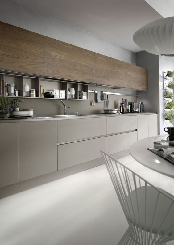 a grey kitchen with wooden cabinets and a grey backsplash, with built-in shelves and nickel touches looks very modern