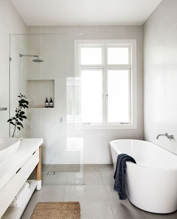 a modern neutral space with a seemless shower space, a free-standing tub, vanity with open shelves and a jute rug
