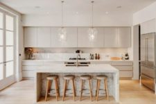 03 a neutral kitchen with cream cabinets, a white kitchen island with marble touches and pendant lamps