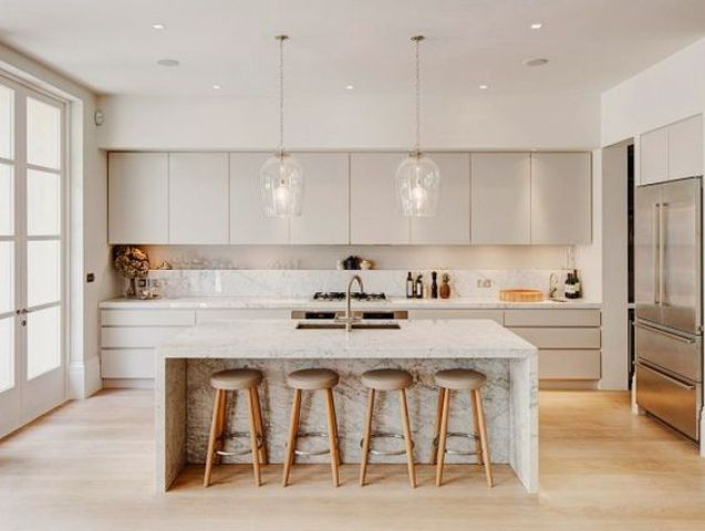 a neutral kitchen with cream cabinets, a white kitchen island with marble touches and pendant lamps