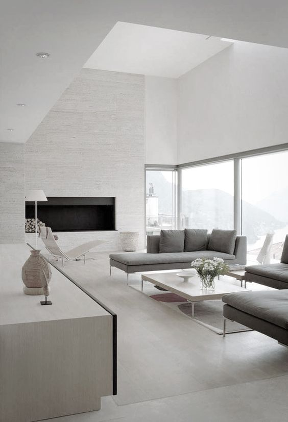 a neutral space with a textural fireplace wall, large windows and comfy grey furniture
