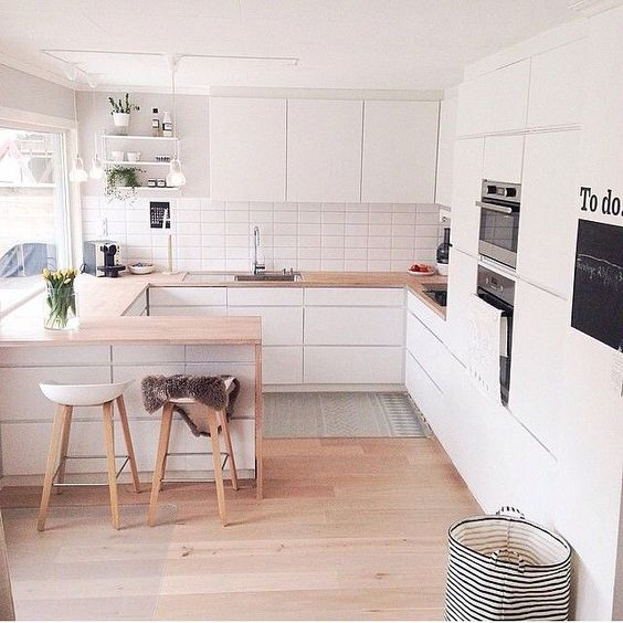 a small U-shaped kitchen done in white with a breakfast space and cooking zone in one