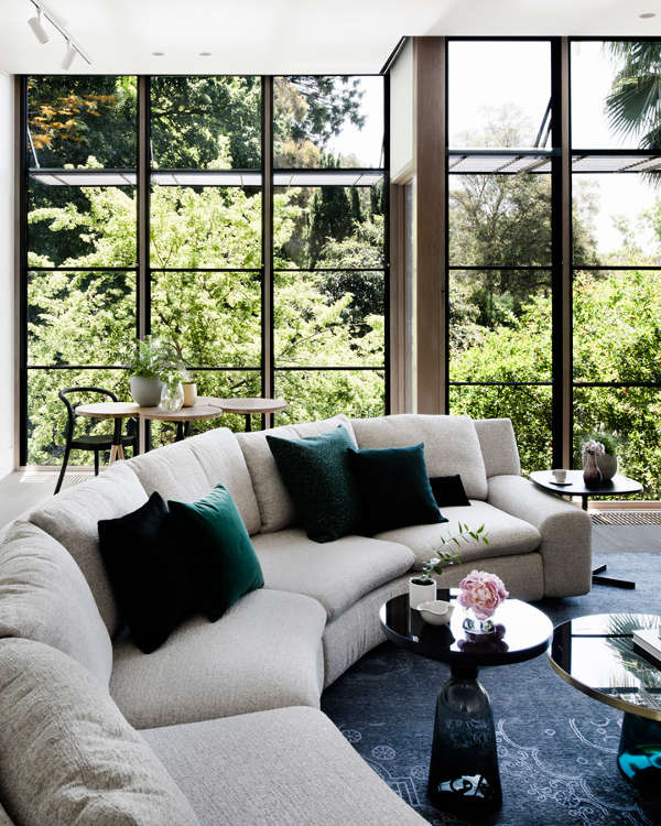 The living room features a framed glazed wall, a large rounded sofa, a breakfast zone