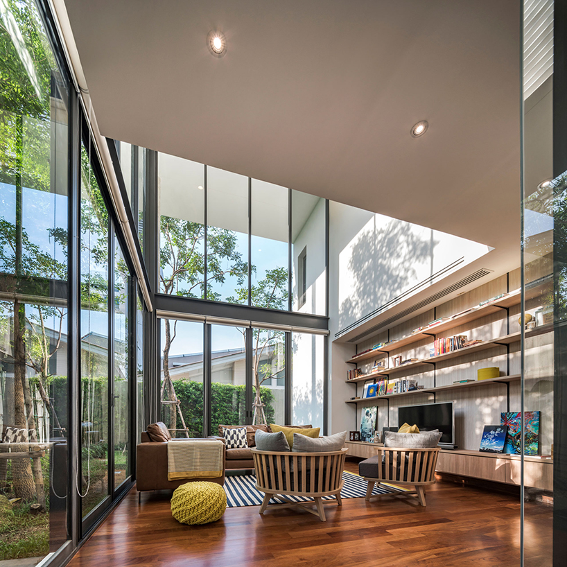 The living room features extensive glazing, a large shelving unit, a sitting space that seems to be outdoors due to the strong connection with it