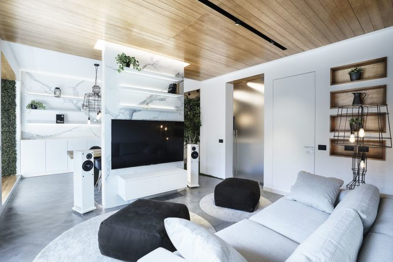 The living room is light-colored, light grey and white, with black touches and open shelving