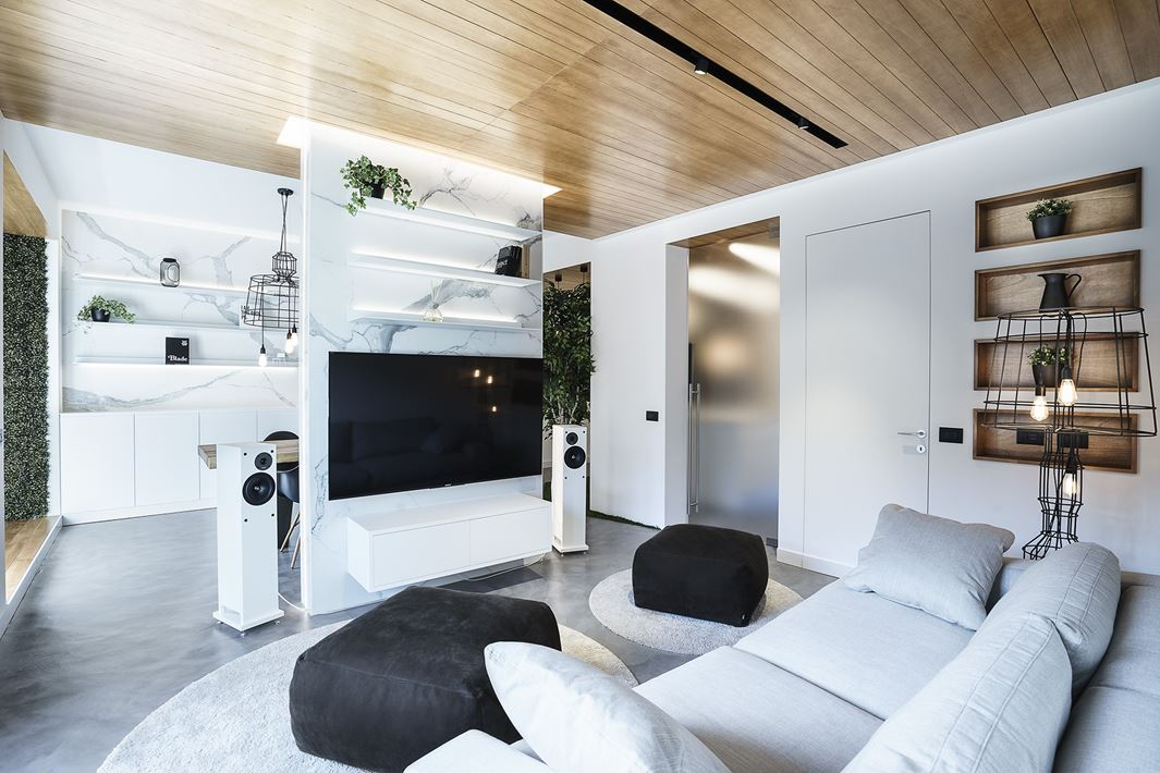 The living room is light colored, light grey and white, with black touches and open shelving