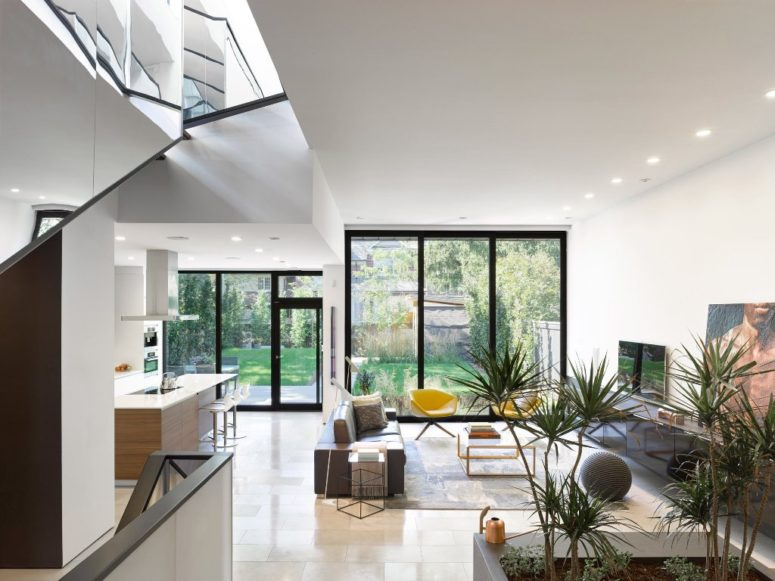 The living room is united with the kitchen and features a glazed wall, greenery and simple modern furniture