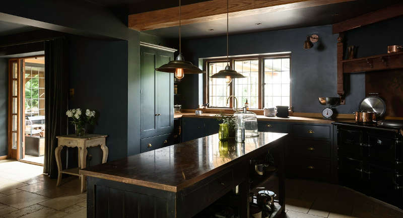 There's a large kitchen island with storage, some vintage accessories like scales and industrial pendant lamps