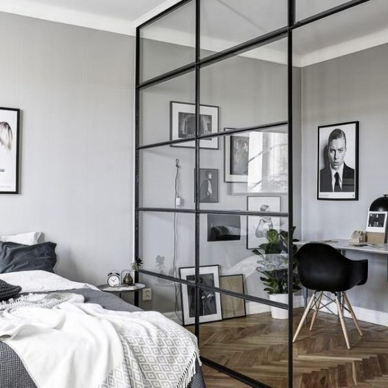 a masculine bedroom and a workspace separated with a glazed framed wall