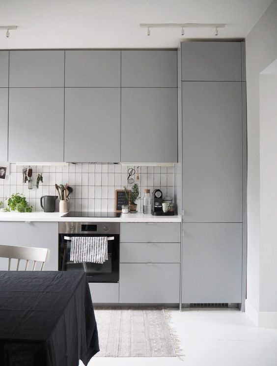 A Modern Light Grey Kitchen With A White Tile Backsplash Made Stand Out  With Black Grout