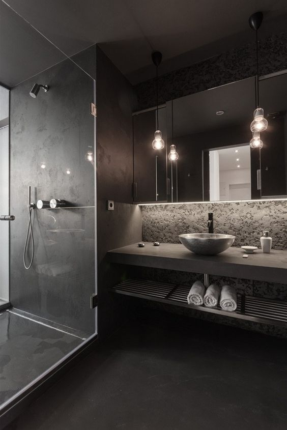 a modern moody space with a stone wall, a concrete vanity shelf, a matte black shower and floor