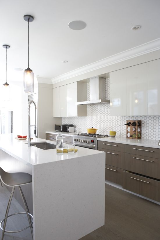 a modern space with sleek white cabinets and wooden ones, a geo tile backsplash and a marble kitchen island
