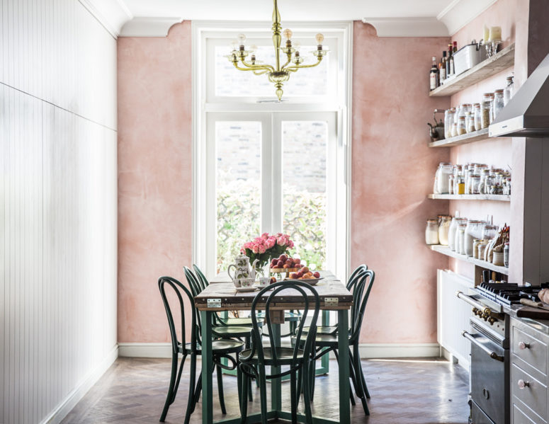 a vintage-inspired kitchen and dining zone with a pink wall looks very cute