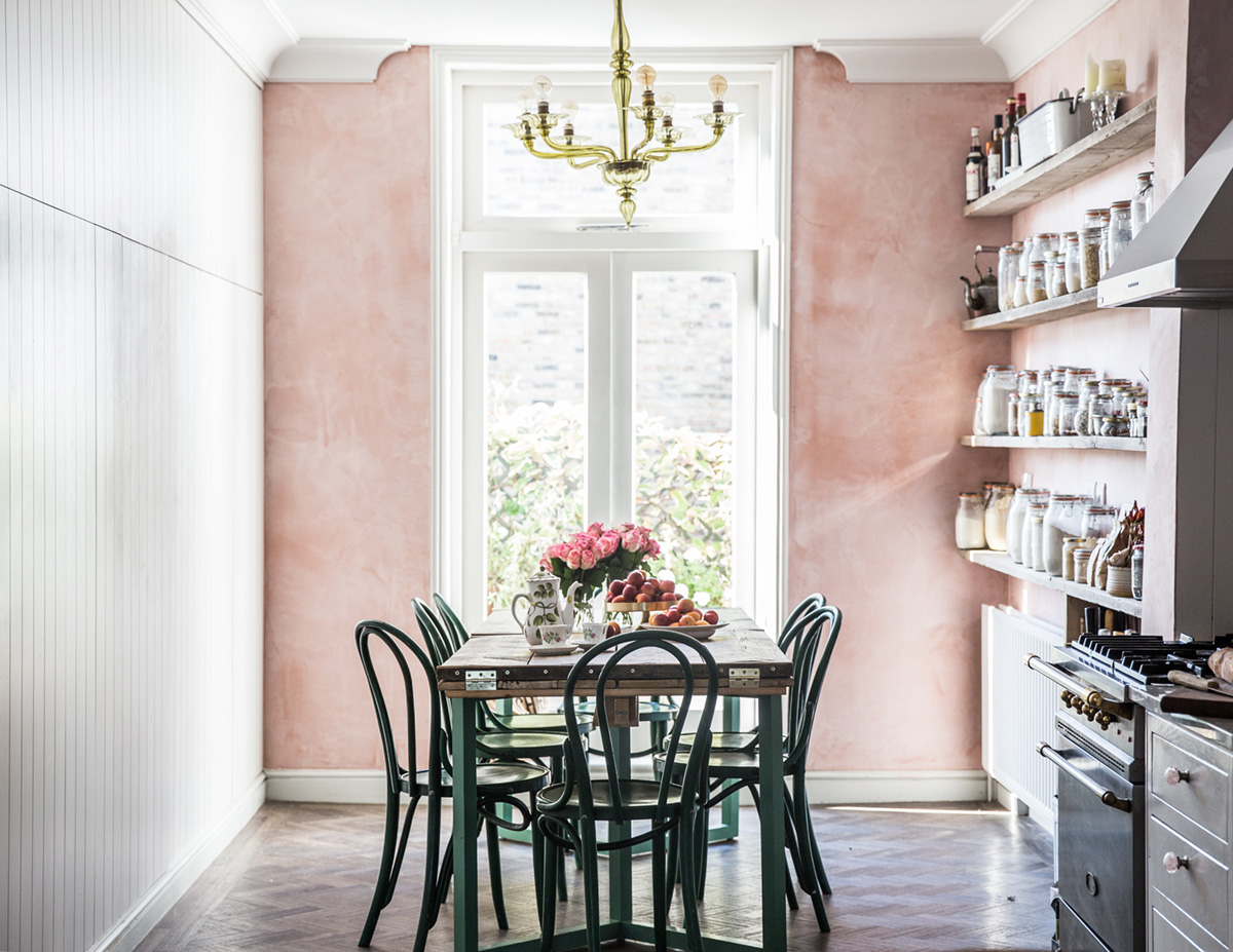 a vintage inspired kitchen and dining zone with a pink wall looks very cute