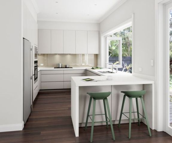 a white U-shaped kitchen with a breakfast zone and a large window
