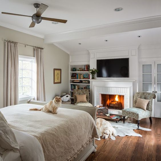 a whitewashed brick fireplace brings extreme coziness to the bedroom